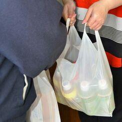 弁当や飲み物などが入った袋を受け取る利用児童の母親(右)=20日、那覇市内
