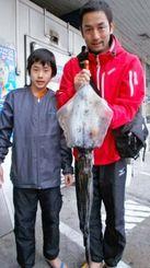 9日、伊計島で2.33キロのシルイチャーを釣った古賀義之さん(右)