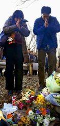 事故現場で献花し、手を合わせる遺族=16日午後、長野県軽井沢町