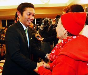 当選を喜び支持者と握手する松本哲治氏(左)=12日午後10時5分、浦添市屋富祖の選対事務所