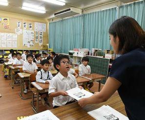1学期の終業式で、初めて「よい子のあゆみ」をもらい、緊張と喜びいっぱいの中の町小学校の1年生=8日午前9時すぎ、沖縄市上地