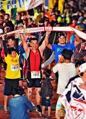 長いレースを終え、家族や友人とゴールする選手たち=23日午後8時すぎ、宮古島市陸上競技場(金城健太撮影)