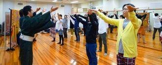 若手演者に組踊の所作を習うツアー参加者=2015年、浦添市の国立劇場おきなわ(近畿日本ツーリスト沖縄提供)