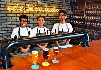 那覇発のクラフトビールで地域の盛り上げを目指す由利充翠代表(右)ら=13日、那覇市牧志・浮島ブルーイングタップルーム