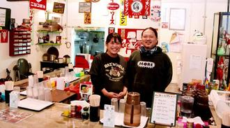 接客に笑顔を絶やさない石川泰央さん(右)と妻麻里子さん。店内は昭和の雑貨が飽きさせない空間を演出している=宜野湾市新城