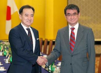 会談を前に握手するモンゴルのツォグトバータル外相(左)と河野外相=22日夜、東京都港区の飯倉公館