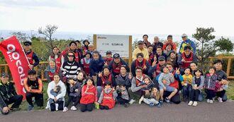 「ドコモの森」記念碑の前で集合する清掃活動の参加者たち=南城市・知念岬公園
