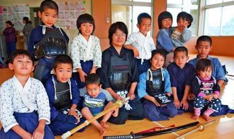 剣道を教える「錬磨会」の子どもたちと梶原治代さん(中央)。この日は居合道と杖道の武道具も持参した=南城市・大里北児童館