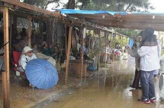 激しい雨の中、新基地建設に抗議する集会を続ける市民ら=13日、名護市辺野古