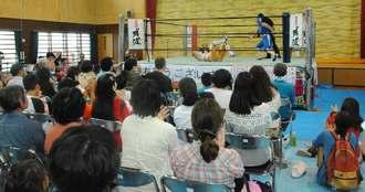 琉球ドラゴンプロレスリングの美ら海セーバー(右)とウルトラソーキの対戦に声援を送る観客=6日、沖縄市知花・美さと児童園体育館
