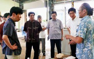 月桃加工施設で担当者から商品の説明を受ける山本一太沖縄担当相(手前左)=21日、北大東村中野