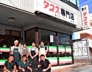 創業時のままの「タコス専門店」の看板が目を引く店舗前で。後列左から2人目がオーナーの儀武直子さん=宜野湾市伊佐