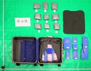 二重底に細工されたスーツケースと銀色の袋に入った覚醒剤(沖縄地区税関提供)
