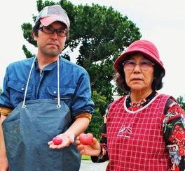 自宅でハート形の紅じゃがいもを収穫した金城文子さん(右)と次男の直さん=伊江村西江上