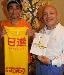 新しいTシャツを手にする又吉永文さん(左)と津嘉山貞雄社長=4月22日、豊見城市我那覇