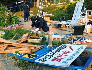 プラカードなどが散乱する辺野古新基地建設に反対する市民のテント村で、鑑識作業をする警察官=20日午前7時ごろ、名護市辺野古、米軍キャンプ・シュワブゲート前