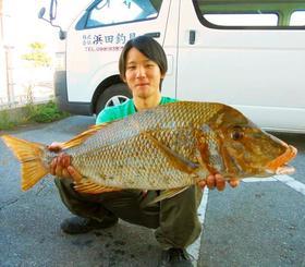 伊計海岸で71センチ、4.12キロのタマンを釣った仲地宗仁さん=19日