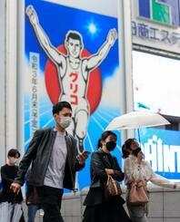 大阪・ミナミを歩くマスク姿の人たち=7日午後5時4分