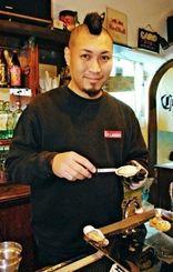 華麗な手さばきでカキを開けるオイスターマイスターの白迫さん=北谷町宮城の「BAR KEYLARGO」