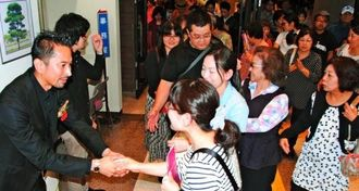上映会後、沖渡崇史さん(左端)に握手を求める来場者=22日午後、嘉手納町・かでな文化センター