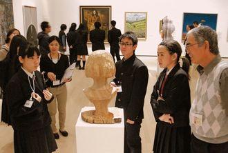 ボランティア(右端)の説明を手話通訳を通じて聞き、さまざまな角度から彫刻を眺める生徒たち=18日、那覇市の県立博物館・美術館