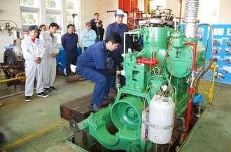 関係者が見守る中、点火された船舶用焼玉エンジン=28日、糸満市西﨑・沖縄水産高校