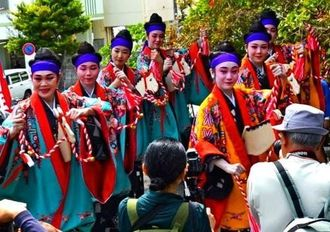 鮮やかな衣装で「じゅり馬」を披露する女性たち=13日、那覇市辻