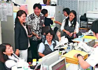 朝礼後の事務所。代表の新城優子さん(左から2人目)は「前は私に来ていた仕事の依頼がスタッフを通して来るようになった。皆が営業マンになっている」=那覇市壺屋、新城優子司法書士事務所
