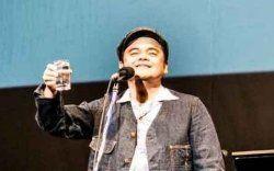 泡盛のグラスで乾杯するボーカルの比嘉栄昇(撮影:浜野カズシ)
