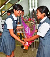 日本ジュニア選手権で優勝し、祝福の花束を受け取る興南高の新垣比菜(左)=那覇空港
