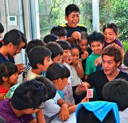カードマジックを披露するMASAさん(右端)=8日、竹富町立波照間小中学校