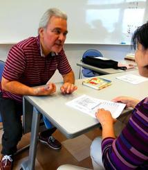 健康教室の受講者に中医学の理論に基づいて体質に合った食事や漢方薬をアドバイスする長嶺荒人さん(左)=浦添市、てだこホール多目的室