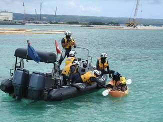 工事現場に近づこうとするカヌー隊を拘束する海上保安官。後方は工事が進む「K4」護岸=名護市辺野古沖