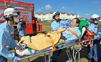 災害時を想定し被災者の救助訓練をする消防隊員=29日、金武町のキャンプ・ハンセン
