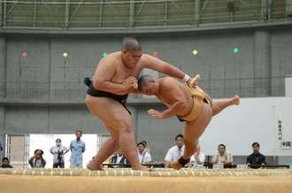 相撲団体 中部農林の城間瑠正(左)が北部農林の川畑六満を上手投げで破る=うるま市具志川ドーム