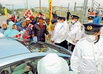 ゲートに入る車を止めようとする市民と警官がもみ合う=28日午前7時39分、名護市辺野古のキャンプ・シュワブ前