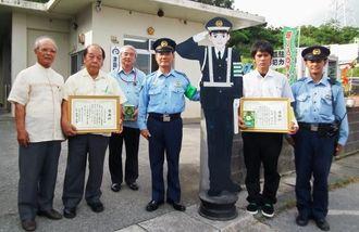 防犯看板の警察官の立ち見姿を製作した宮城雄平君(右から2番目)=中城村津覇駐在所前