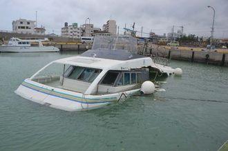 半分が海に沈んだダイビング船=登野城漁港