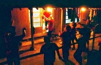 渡名喜村の伝統行事ウバニクーイで、歌と踊りで屋敷を褒めたたえる人々と、踊りで返礼する家主=9日、村内(吉田勇一郎通信員撮影)