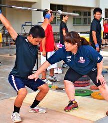 城内史子コーチ(右)が見守る中、練習に取り組む高校生=糸満高校
