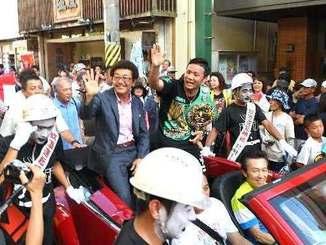 大勢の市民に迎えられ、オープンカーでパレードする比嘉大吾選手と具志堅用高会長=11日午後4時22分、宮古島市の西里通り