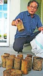 ガマから遺骨とともに出てきた空き缶を手にする仲原館長=今帰仁村歴史文化センター
