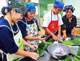 地域の人に教わりながら、ムーチーを作る生徒たち=27日午後2時半ごろ、糸満市・高嶺中学校(国吉聡志撮影)