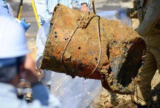 新たに見つかったドラム缶の一つ。調査員がビニール袋に入れ、サンプルを採取した=29日午後1時50分ごろ、沖縄市上地・市サッカー場