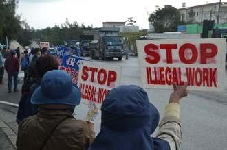 資材を運び入れるダンプカーに抗議する人々=26日午前10時ごろ、名護市辺野古の米軍キャンプ・シュワブゲート前