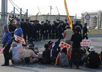 米軍キャンプ・シュワブゲート前に座り込んで抗議する市民ら=18日午前8時17分、名護市辺野古