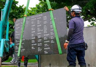 戦没者の名前が新たに追加された「平和の礎」の刻銘板を設置する作業員=15日、糸満市摩文仁・平和祈念公園内