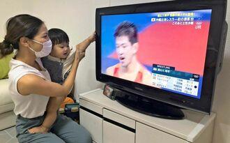屋比久翔平選手をテレビで見守る妻の加奈子さんと長男紫琉ちゃん=3日、横浜市内の自宅(提供)