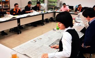 紙面を読み、気になる記事を探す受講者=3月30日、那覇市のエレドック沖縄本社