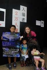 来場2万人目の橋本直美さん(後列右)家族=23日、豊見城市・沖縄アウトレットモールあしびなー